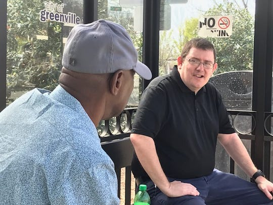 Ronny Johnson and Billy Burgess chat while waiting for their bus on South Pleasantburg Drive.