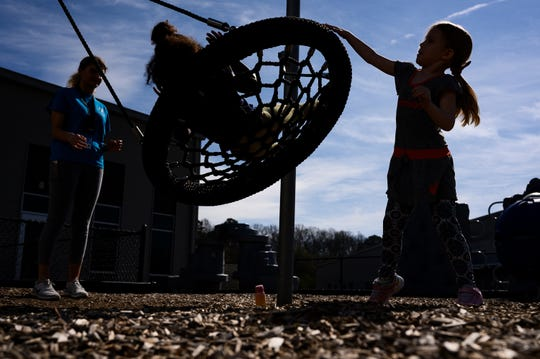 Counselor Charlotte Christiansen and Carmen Jones, 6, push Anslee Ramsey, 5, on a swing at the Powdersville YMCA Friday, March 20, 2020.