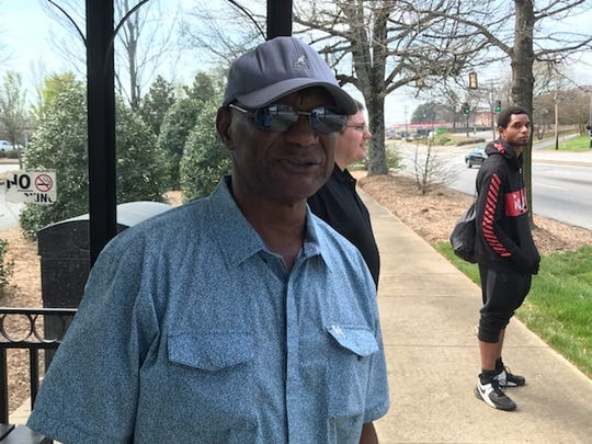 Ronny Johnson waits for his bus on South Pleasantburg  Drive.