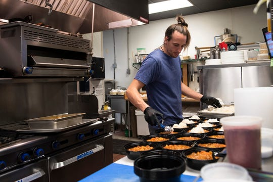 Preston Dierickx prepares takeaway dishes of gumbo at Topsoil Kitchen and Market Friday, Mar. 20, 2020.