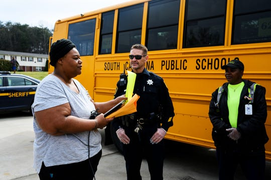 Jalisa White seeks guidance on how to connect to the onboard WiFi at a school bus meal site so that her son Anthony can download his schoolwork at Boulder Creek Apartments Thursday, March 18, 2020.