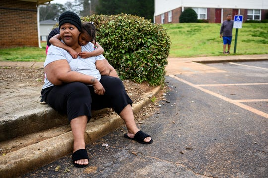 Jaylah White, 6, hugs her mother Jalisa as they wait for the Greenville County Schools mobile meal site to restock with packaged meals at Boulder Creek Apartments Thursday, March 18, 2020.