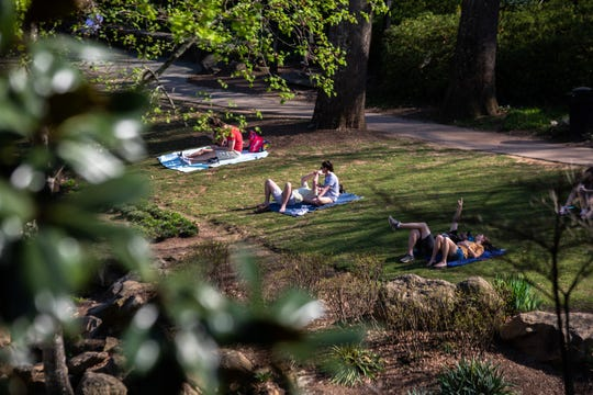 Couples lie on blankets in Falls Park in downtown Greenville, Friday, March 20, 2020, the same day South Carolina Department of Health and Environmental Control announced an additional 45 cases of the COVID-19 novel coronavirus bringing the statewide total to 124 cases in 25 counties.