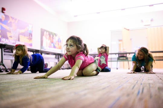 Caroline Adkins, 5, and other children participate in a yoga instruction at the Powdersville YMCA Friday, March 20, 2020.  The daycare stayed open especially for children of essential workers.
