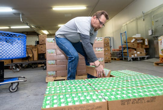Kris Harding unpackages and stacks cases of milk at the Great Falls Food Bank on Friday afternoon.