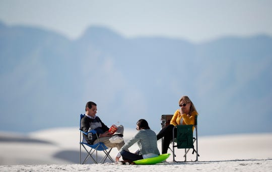 In this March 5, 2020, photograph, visitors relax on a gypsum dune in White Sands National Park at Holloman Air Force Base, N.M. Most national parks are open as a refuge for Americans tired of being stuck at home because of the coronavirus. Entry fees have been eliminated, but many parks are closing visitor centers, shuttles and lodges to fight the spread of the virus. (AP Photo/David Zalubowski)