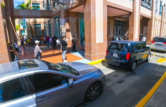 Walk-in customers line up outside the Bank of Guam, Hagåtña branch, as traffic also builds up for the bank's drive-up window, on Friday, March 20, 2020. Due to COVID-19 concerns, tape markings were spaced apart and applied to the sidewalk outside and only 15 customers at a time were being entertained by tellers inside the bank, as measures to promote social distancing at the financial institution.
