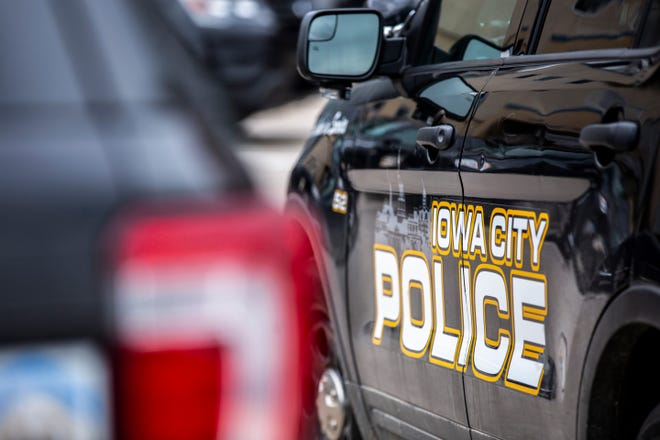 Iowa City police cars are parked outside, Friday, March 20, 2020, in Iowa City, Iowa.
