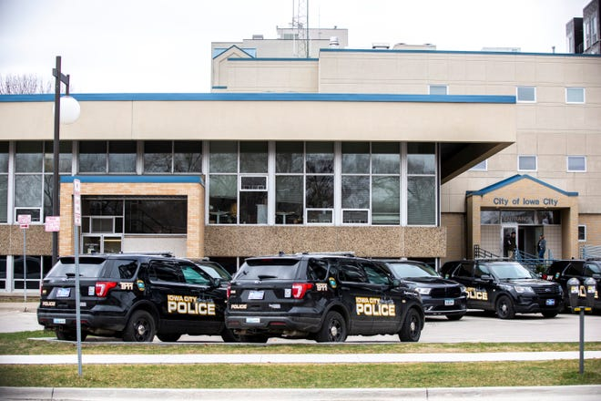 Iowa City police cars are parked outside City Hall, Friday, March 20, 2020, in Iowa City, Iowa.