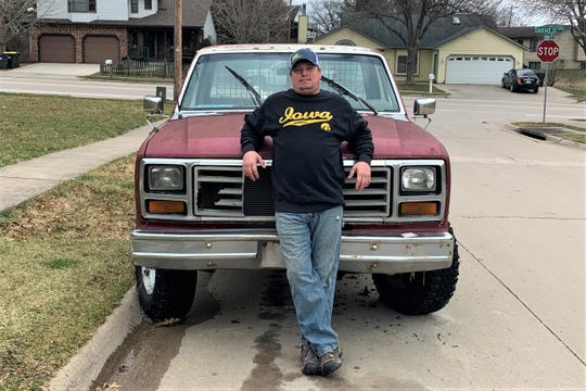 Adam Clark, 37, of Iowa City used his 1982 red F-150 to lend hand to someone stuck in a ditch during the COVID-19 pandemic. He stands in front of his truck on March 20, 2020.
