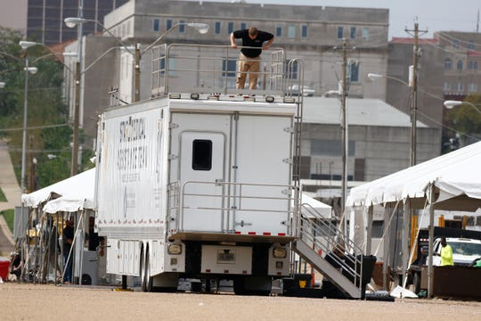 A worker secures a railing on the State Medical Assistance Team's Mobile Field Hospital at the Mississippi State Fair Grounds, Thursday, March 19, 2020, in Jackson, Miss. The tents and field hospital were set up at the fairgrounds as it has area to handle the coronavirus response. (AP Photo/Rogelio V. Solis)
