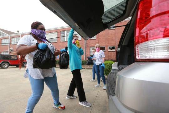 Ayana Westmoreland, left, gets ready to put two full bags of food into the rear gate of an SUV at First United Methodist Church in Tupelo, Miss. on Thursday.
