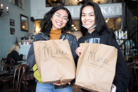 JC Holdway workers Hannah Mendoza, left, a server, and Abish Mendoza, a host, hold up care packages they picked up at The French Market in Knoxville, Tennessee on Friday, March 20, 2020. Both said they have lost many of their shifts due to declining traffic at the restaurant. Those who are eligible may pick up a care package between 11am and 3pm at the downtown location.