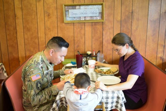 From left, Art Guzman, his son Adriel, 3, and health care provider and friend Jenny Jones say a prayer before their meal at Colonel's Cafe on Newcom Ave. in Knoxville, Tennessee on Friday, March 20, 2020. Guzman said he is taking all the necessary precautions to stay safe and healthy during the coronavirus pandemic, and that getting out of the house for a meal with his son is part of his way of coping for his mental health.