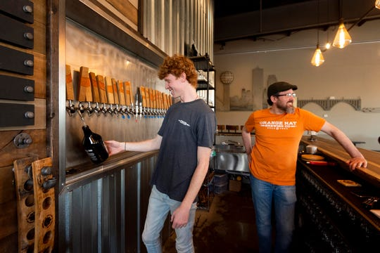 Chris Taylor, left, fills a growler for a customer at ORange Hat Brewing on Thursday, March 19, 2020. The brewery's tasting room is closed but still selling their beer to go. At right is Chris Travis.