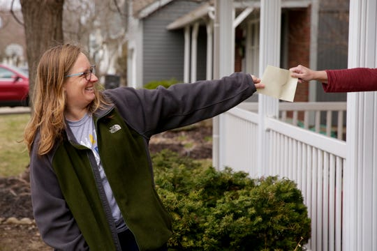Kathy Parker reacts as she and Amy Austin, not pictured, jokingly practice social distancing while Austin passes along an envelope with gift cards for groceries, Friday, March 20, 2020 in West Lafayette.