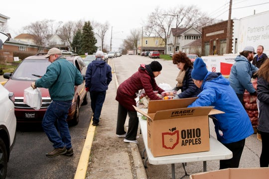 Food Finders Food Bank volunteers load cars at a drive-thru pantry outside of Linwood Elementary School, Friday, March 20, 2020 in Lafayette.