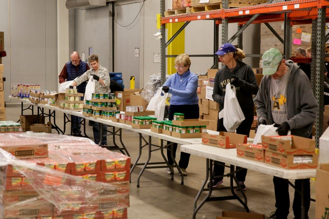 Food Finders Food Bank volunteers pack bags with pre-packaged cans and dried foods at the food bank's warehouse, Friday, March 20, 2020 in Lafayette.