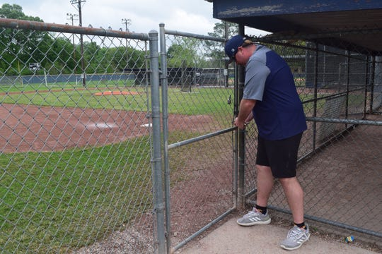 Patrick Painter, Little League board member and parent, locks up the fields as the temporary suspected season begins. He said the decision was based on recommendations fromLittle League International, the organization that oversees the sport.