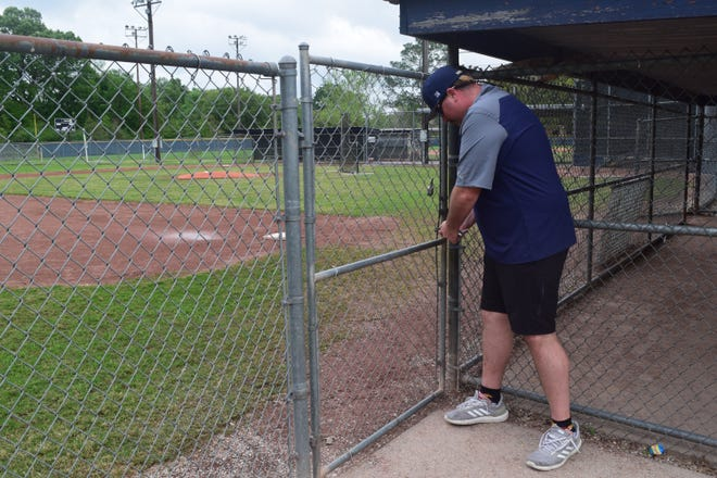 Patrick Painter, Little League board member and parent, locks up the fields as the temporary suspected season begins. He said the decision was based on recommendations from Little League International, the organization that oversees the sport.