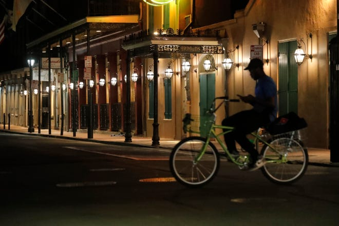"""A view of the nearly deserted Bourbon Street, which is normally bustling with tourists and revelers, in the French Quarter of New Orleans, Thursday, March 19, 2020. New Orleans Mayor LaToya Cantrell issued a mandatory """"stay home"""" order for the city on Friday afternoon."""