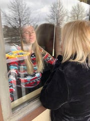 Kristyn Hickey placed herself in self-isolation after returning from Spain. Here, she visits with her mother, standing outside of the hotel room.