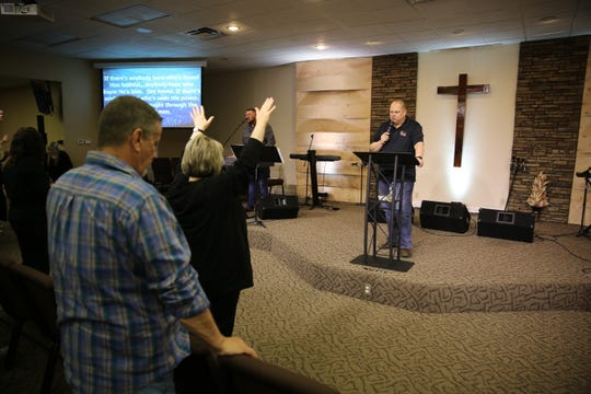 At Harlan County's Harvest Worship Center during a Wednesday night service, people spread out among the pews for a service. Pastor Bo Lee has since decided to hold services online.