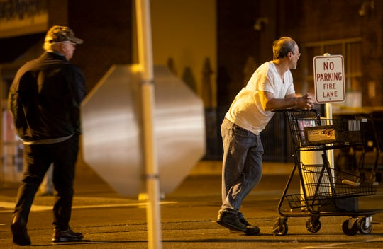 Two men wait outside the Kroger on Breckenridge Lane in Louisville on Friday morning. The scene was much calmer than the day before when shoppers rushed the doors.