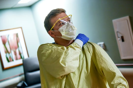 Registered nurse Eric Eiseler adjusts his protective gown before going into a room on the floor housing patients with low to moderate COVID-19 risk on Thursday, March 19, 2020, at Sparrow Hospital in Lansing. Medical staff puts on protective gowns, gloves, a mask and eye protection before entering rooms. No patients on the floor had tested positive for the coronavirus as of that afternoon.