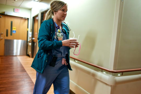 Charge nurse Lindsay Muenchen gets water ready for a patient on the floor housing those with low to moderate COVID-19 risk on Thursday at Sparrow Hospital in Lansing.