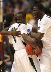 (L-R) Kalin Lucas #1, Travis Walton #5 and Draymond Green #23 of the Michigan State Spartans celebrate after their 74-69 win against the USC Trojans during the second round of the NCAA Division I Men's Basketball Tournament at the Hubert H. Humphrey Metrodome on March 22, 2009 in Minneapolis, Minnesota.