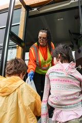 Bus driver Lois Partipilo hands out free lunches to children in the Marion City School District Thursday. The school district is delivering thousands of free lunches and breakfasts to school-age children during the state-ordered shut-down of school buildings during the public health emergency caused by coronavirus.