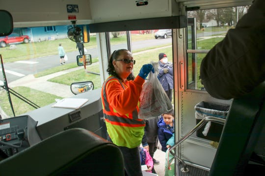 Bus driver Lois Partipilo passes out free lunches and breakfasts to children Thursday at Plantation and Rodney drives in Marion. Marion City Schools is delivering free meals to children in the district while schools are closed for the coronavirus crisis.
