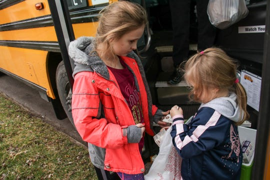 From left to right, Aeris Dixon, 9, and Quistis Mackenzie, 6, put milk into their grab-and-go lunch bag Thursday at a stop at Bennett Street and Uncapher Avenue in Marion. Marion City Schools is delivering thousands of breakfasts and lunches to school-age children during the state-ordered shut-down of school buildings for the coronavirus pandemic.