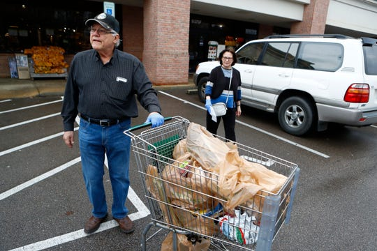 Vince Alfonso, 74, and his wife Sally, 72, exit the Germantown Fresh Market after shopping on Friday during a recommended 'senior only' shopping hour from 8 to 9am at the grocer. The Fresh Market Corporate Office refused to allow access inside of their store for reporting, though shoppers said they saw no signs of carts being sanitized in between use, glove dispensers or signage detailing suggestions for social distancing or hygiene practices.