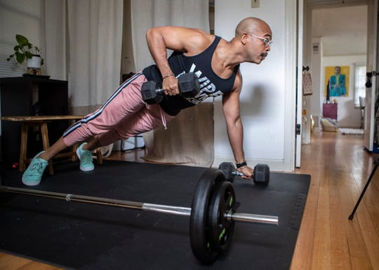 Fitness instructor David Quarles does weighted push ups in his home gym in response to the coronavirus on Thursday, March 19, 2020.