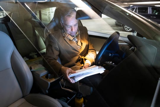 Because he just returned from a week-long trip to California, attorney Michael Sperling works from his car Friday, March 20, 2020 in the parking ramp of the 100 East Wisconsin Building in Milwaukee, Wis. His office is in the building, and working in the parking ramp allows his legal assistant to bring him papers he needs to sign, coffee and other items.