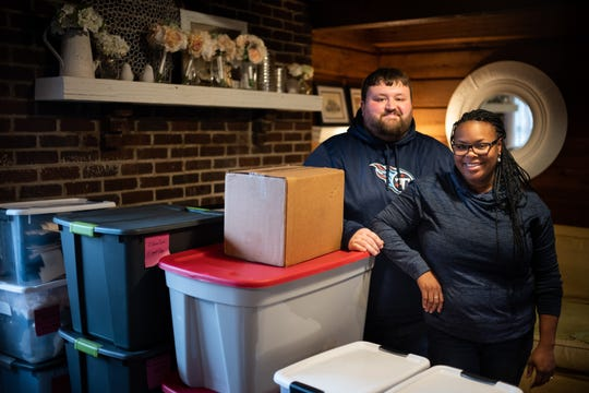 Joe Levickis and Danyelle Valentine with boxes containing items for their wedding, now in storage at their home in Joelton.