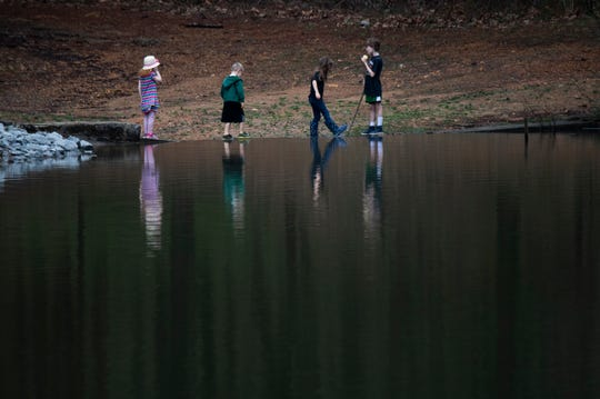 Children play at the edge of Lake Van at Bowie Nature Park Friday, March 20, 2020 in Fairview, Tenn.