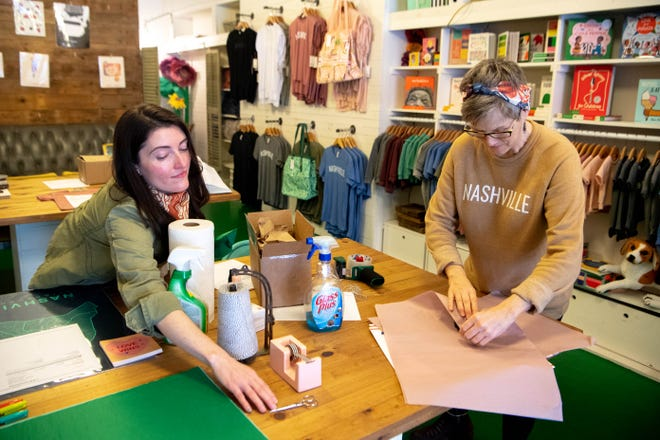 Courtney Webb, left, and Liz Dineen prepare online orders to be shipped at Hey Rooster General Store Thursday, March 19, 2020, in Nashville, Tenn. Due to the coronavirus, Hey Rooster shut their doors and is only taking online orders with pick-up, delivery or shipping.