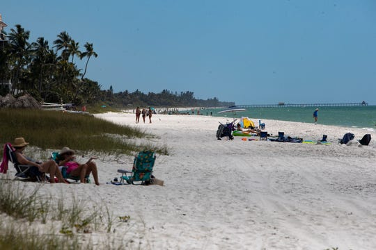 Community members and visitors spend time on the beach Friday, March 20, 2020, in Naples.
