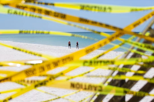 Beachgoers walk along the shore near the Naples Pier on Friday, March 20, 2020. The city of Naples closed the Naples Pier and public beach accesses Wednesday.