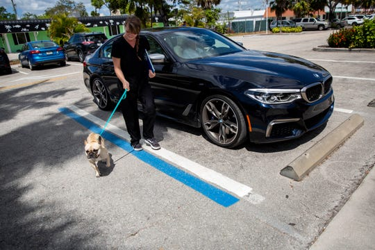 Ashley Drabczyk, certified veterinary technician, walks Bruno, a 2-year-old French bulldog, from his car into Naples Coastal Animal Hospital on Friday, March 20, 2020.