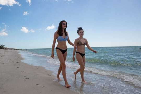 Lillian Sanderson, left, and her sister Aubrey Sanderson, both visiting from Minneapolis, Minnesota, take a walk along the beach, Friday, March 20, 2020, in Naples.