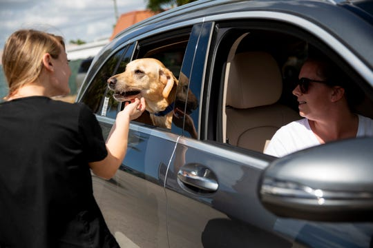 Ashley Drabczyk, left, certified veterinary technician, pets Tripp, a 2-year-old golden lab, as she talks to Amy Hule, right, outside Naples Coastal Animal Hospital on Friday, March 20, 2020. The animal hospital is offering curbside veterinary services rather than allowing owners to come inside the building in order to prevent the spread of COVID-19.