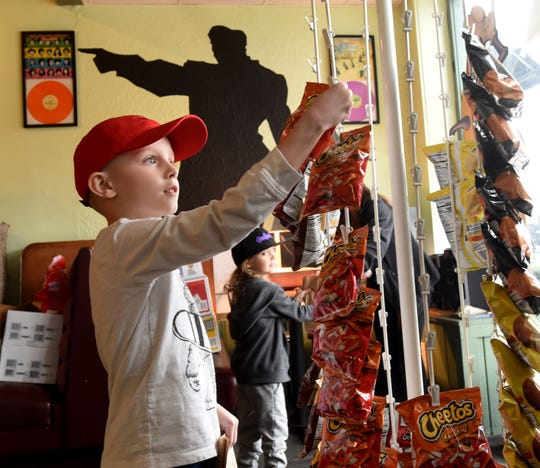Talon Rhodeback, 7, selects his choice of chips as sibling Theo, 5, gets his hot dog from Frank and Sammies in downtown Newark. Kids got a free hot dog, bag of chips, piece of fruit, and water to go as a way to help those dealing with the unexpected closure of local schools.