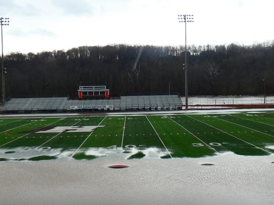 Water slowly begins to recede Friday afternoon in Heath after torrential rain caused the flooding of Licking View Drive and adjacent areas, including Swank Field at the high school.