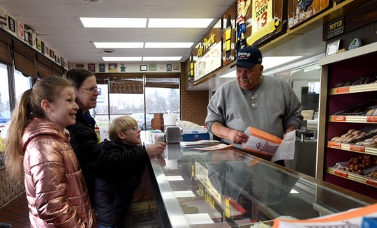 Louise Jackson brings her grandkids Ella and Gavin in for their donut and choice or milk, orange juice, or hot chocolate from Jolly Pirate Donuts owner Leroy Vannest. The Newark donut shop is offering kids a free breakfast between 7 a.m. and 9 a.m. during the schools closure.