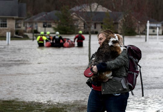 Sue Marie Bellis holds her dog Sadie after their were rescued by boat by first responders. Her home in Glenwood Apartments flooded due to heavy rains overnight.