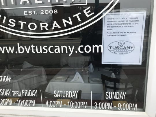 Sign on window of the B.V. Tuscany Italian restaurant on Cedar Lane in Teaneck on Friday, March 20, 2020, announcing that the restaurant is closed because of health concerns over the coronavirus threat.  Inside, the tables are still set for customers.